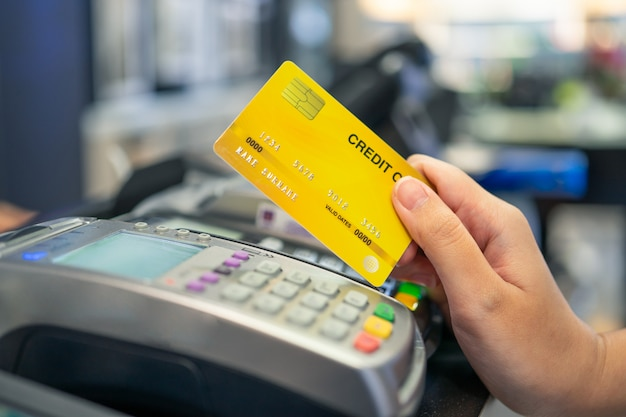 Kreditkarten-schlagmaschine und eine junge person, die eine kreditkarte hält, um für käufe zu zahlen