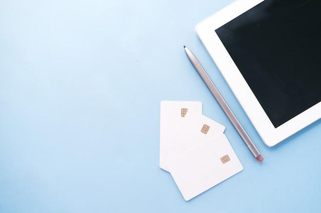 Kreditkarten und digitales tablet auf blauem hintergrund
