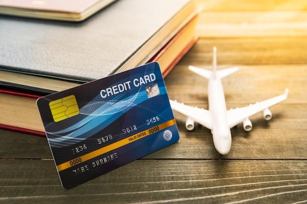 Kreditkarten- und flugzeugmodell auf holztisch vorbereitung für das reisekonzept