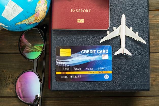 Kreditkarten- und flugzeugmodell auf holztisch, vorbereitung für das reisekonzept