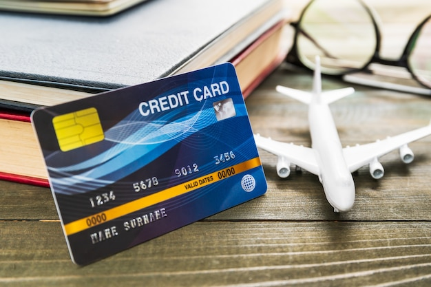 Kreditkarten- und flugzeugmodell auf holztisch