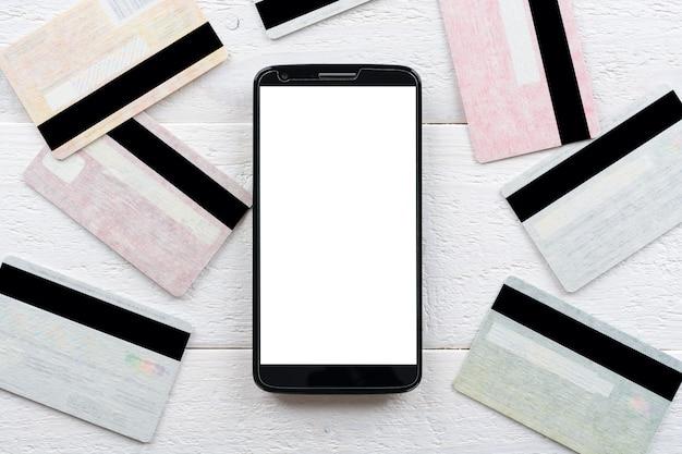 Kreditkarten und smartphone liegen auf einem holztisch