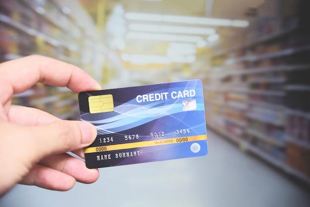 Kreditkarteneinkaufen im supermarkt - übergeben sie das halten der kreditkartezahlung