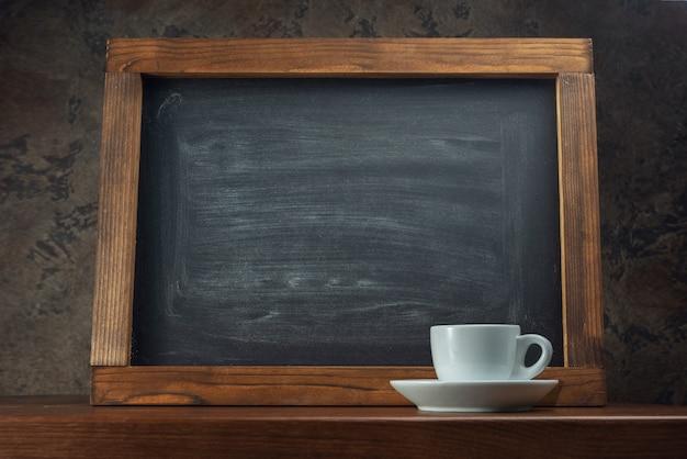 Kreidebrett auf dem tisch und eine tasse kaffee