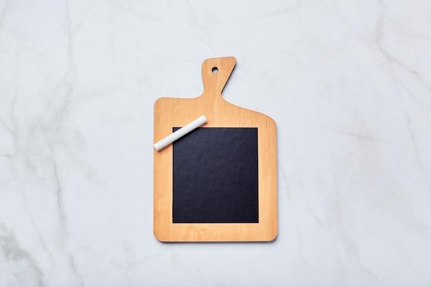 Kreidebrett in form eines küchenschneidebretts mit kreidestück auf hellem marmortisch. tafel zum schreiben von notizen, listen, rezepten
