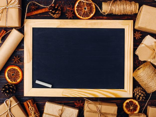 Kreidebrett mitten in geschenken der getrockneten orange, des zimts, der kiefernkegel, des anises auf einem weißen tabellenweihnachtsbillet, sparen raum, draufsicht, platz für text.