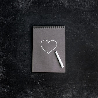 Kreideherz in einem notizbuch das konzept einer valentinstagskarte. flache lage, draufsicht