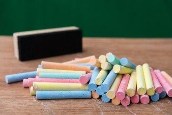 Kreiden in einer Vielzahl von Farben und bürsten auf Tabelle mit grünem Hintergrund, zurück zu Schulbetrug