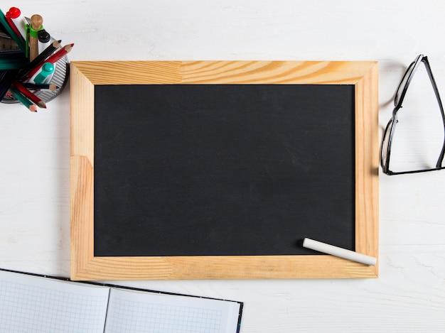 Kreidetafel, gläser und kreide auf dem weißen tisch, kopierraum.