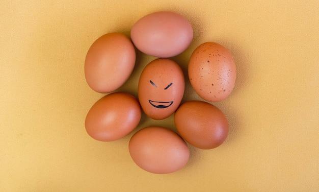 Kreis aus ei mit brauner schale, die mittlere farbe mit schwarzer tinte im smile face-thema, auf dem hintergrund