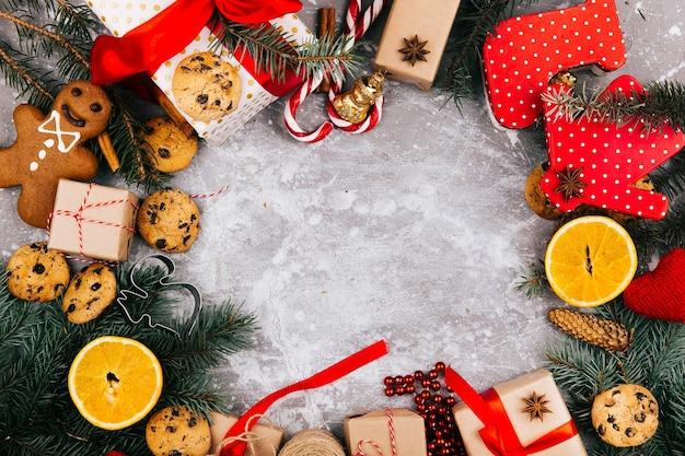 Kreis aus orangen, kekse, tannenzweigen und roten geschenkkartons