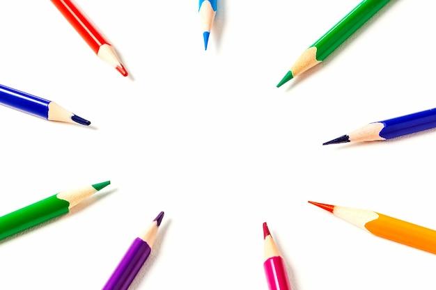 Kreis der angespitzten buntstifte. der fokus liegt auf dem kopierraum in der mitte. bleistifte zeigen auf