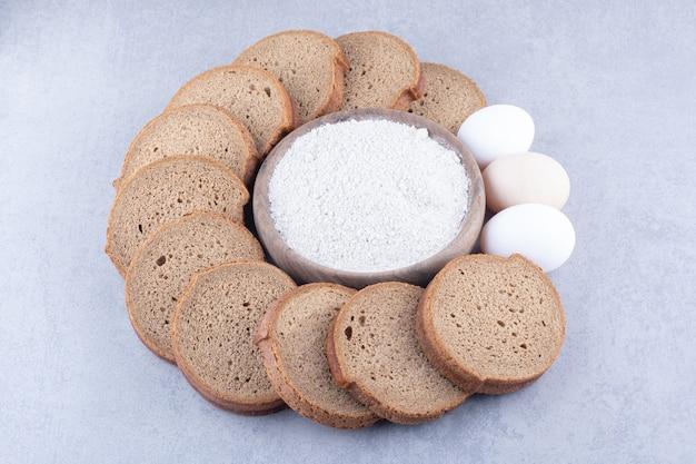 Kreis von geschnittenem schwarzbrot und eiern um eine schüssel mehl auf marmoroberfläche