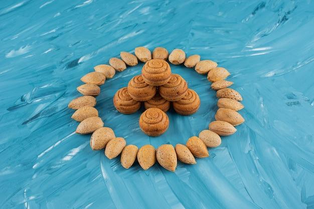 Kreis von mandeln in der schale mit süßen frischen runden keksen auf einem blauen hintergrund.