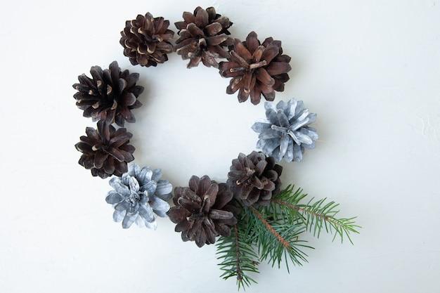 Kreis von tannenzapfen auf einer weißen oberfläche. natürliche weihnachtszusammensetzung. weihnachtskarte. flach liegen. von oben betrachten