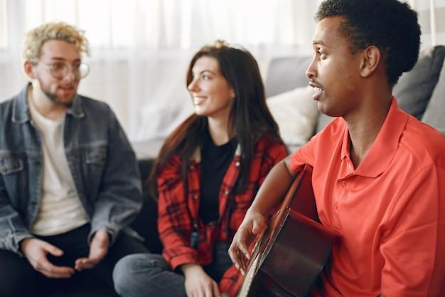 Kreis von verschiedenen frineds zu hause versammelt. ein kerl singt, während er gitarre spielt.