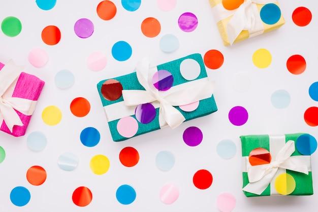 Kreisförmige bunte konfettis auf geschenkboxen gegen weißen hintergrund