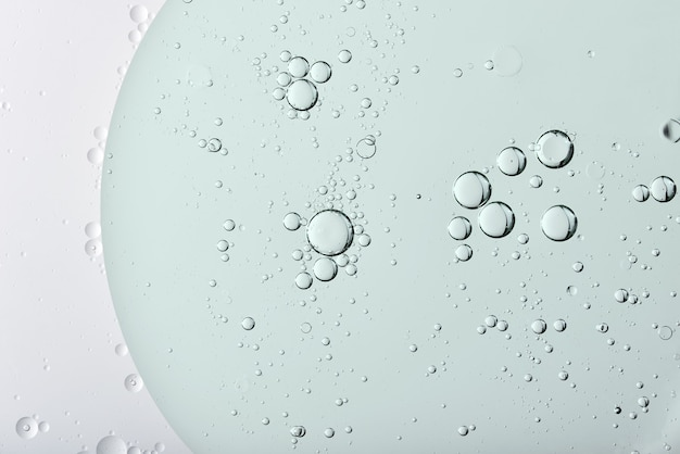 Kreisförmige ölblasen oder -kügelchen auf der oberfläche einer klaren transparenten flüssigkeit von oben in einem zufälligen abstrakten muster in einer vollbildansicht für eine designvorlage