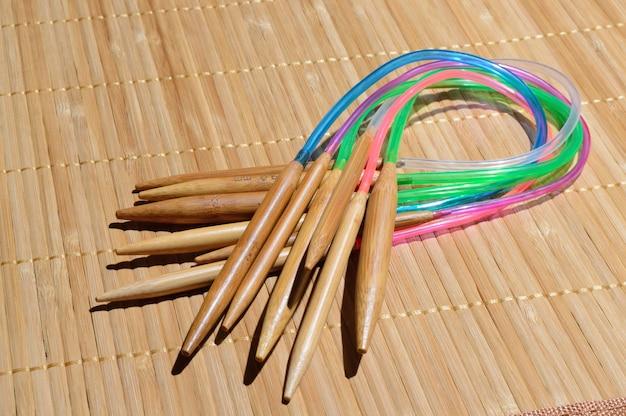 Kreisförmige stricknadeln aus bambus auf einer holzoberfläche.