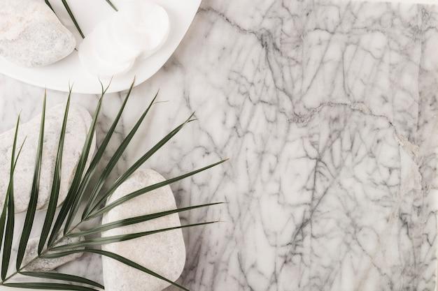 Kreisförmige wattepads; badekurortsteine und palmblatt auf strukturiertem hintergrund des marmors