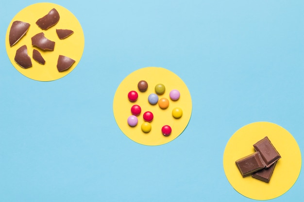 Kreisförmiger gelber rahmen über den bunten edelsteinsüßigkeiten; ostereierschalen und schokoladenstücke auf blauem hintergrund