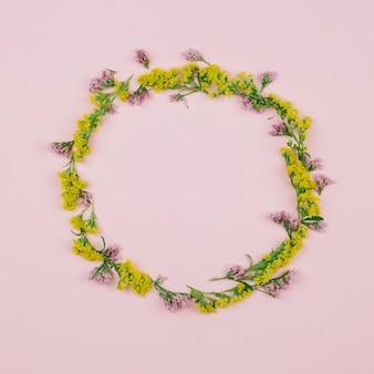 Kreisförmiger leerer rahmen, der mit limonium und gelben goldruten oder solidago gigantea-blumen gegen rosa hintergrund gemacht wird