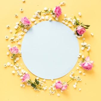 Kreisförmiger leerer rahmen umgeben mit blumen auf gelber oberfläche
