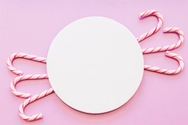 Kreisförmiger weißer leerer rahmen mit weihnachtszuckerstangen entwerfen auf rosa hintergrund