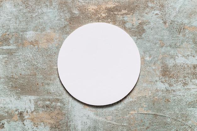 Kreisförmiger weißer rahmen auf altem hölzernem schreibtisch