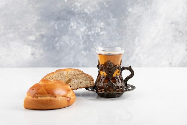 Kreisförmiges gebäck mit einer glasschale schwarzen tees auf einer weißen oberfläche