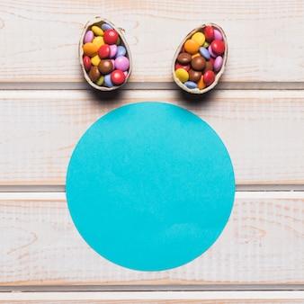 Kreisrahmen des blauen papiers mit ostereiern füllte mit bunten edelsteinsüßigkeiten über dem hölzernen schreibtisch