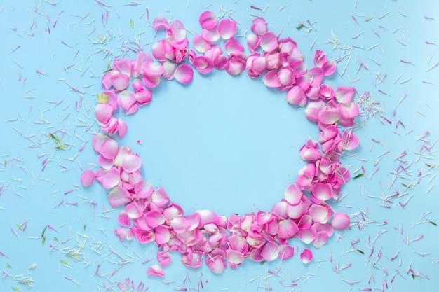 Kreisrahmen gemacht mit den rosafarbenen blumenblättern auf blauem hintergrund