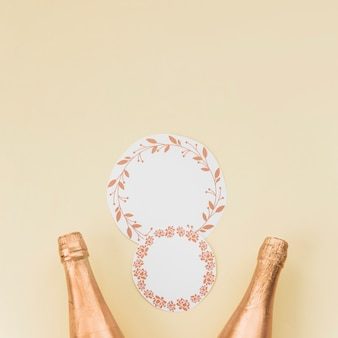 Kreisrahmen mit blättern und blumenmuster nahe zwei champagnerflaschen auf beige hintergrund