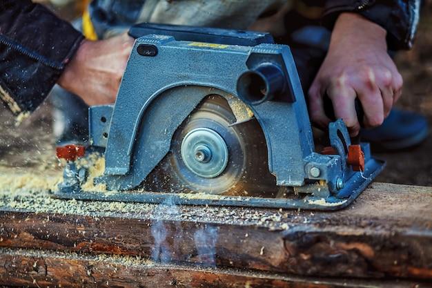 Kreissäge zum schneiden von brettern in die hände des bauherrn, der mann sägebalken, bau- und renovierungs-, reparatur- und bauwerkzeug