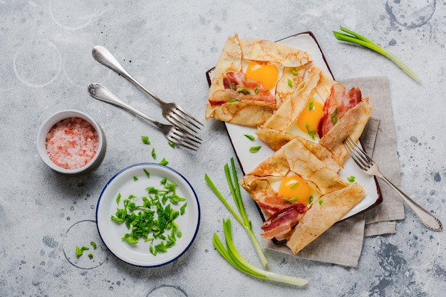 Krepp mit spiegelei, käse, speck und frühlingszwiebeln zum frühstück auf hellgrauer betonoberfläche