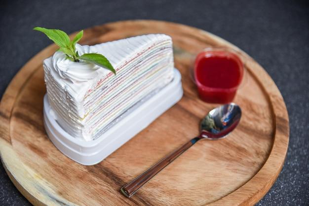 Kreppkuchenscheibe mit erdbeersoße auf hölzernem plattenlöffel und dunkelheit / stück kuchenregenbogen mit schlagsahne