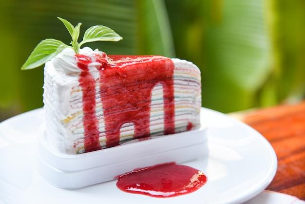 Kreppkuchenscheibe mit erdbeersoße auf weißer platte und naturgrün - stück kuchenregenbogen mit schlagsahne