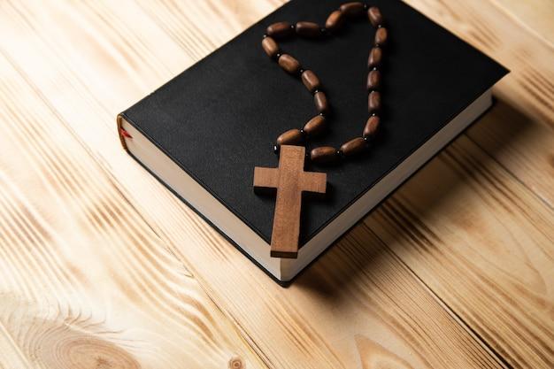 Kreuz auf einem buch auf einem holztisch