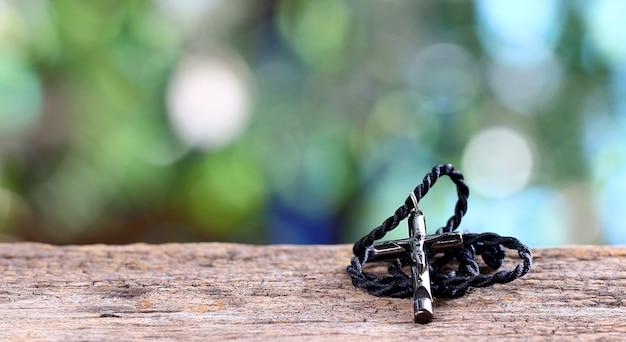 Kreuz halskette auf einem holzspott oben über unscharfem grünem garten bokeh licht