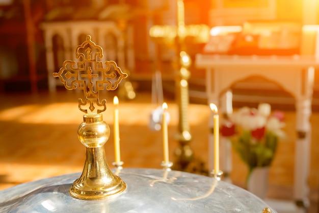 Kreuz in der sonne in der kirche orthodoxes kreuz in der sonne auf dem deckel der schale für den ritus der kindertaufe
