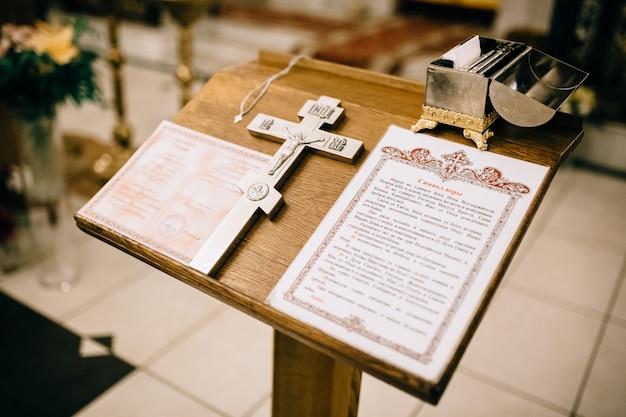 Kreuz und bibel auf einem holzregal