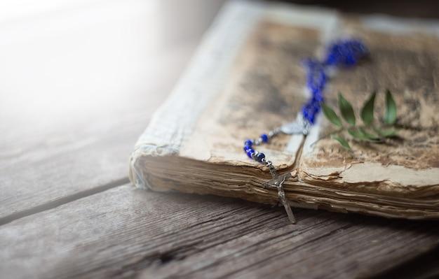 Kreuzen sie auf der antiken bibel auf einem holztisch. heilige bo
