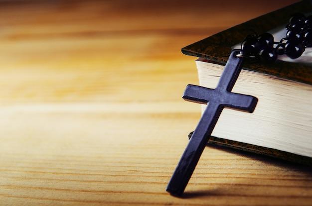 Kreuzen sie auf einem thread mit schwarzen perlen mit einer bibel auf einem holztisch.