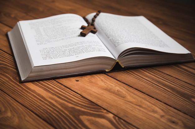 Kreuzen sie die bibel auf einer dunklen oberfläche an