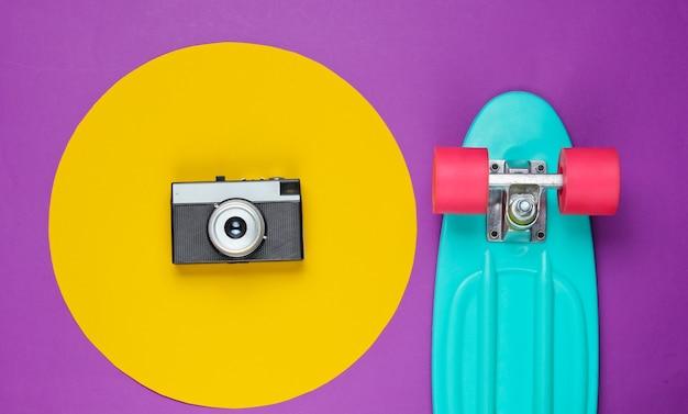 Kreuzerbrett und retro-filmkamera auf lila mit gelbem kreis