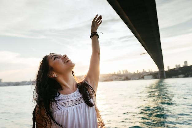 Kreuzfahrtschiff-urlaubsfrau, die reiseferien auf see genießt. freies sorgloses glückliches mädchen, das ozean mit offenen armen in freiheitspose betrachtet.