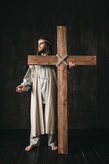 Kreuzigung jesu christi, symbol der christlichen religion. mann mit kreuz auf schwarz