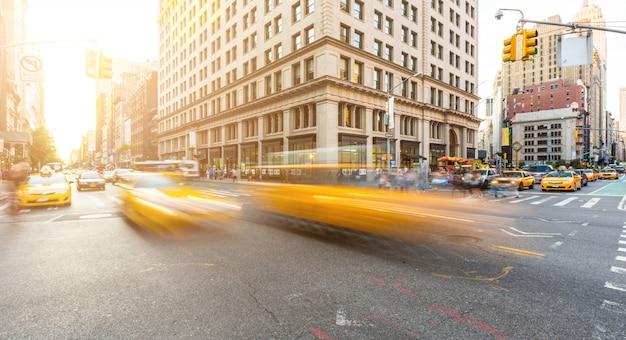 Kreuzung der verkehrsreichen straße in manhattan, new york, bei sonnenuntergang