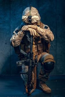 Krieg, armee, waffenkonzept. privater militärunternehmer, der gewehr hält