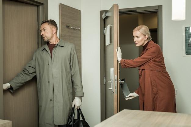 Kriminalität aufmerksam untersuchen. inspektor bringt schwarzen kleiderbügel an der tür an, während ihre arbeitskollegin ordentlich einen anderen raum betritt